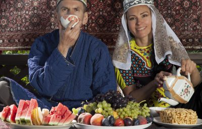 Couple dressed in Oriental clothes have breakfast with fruits and flat cake