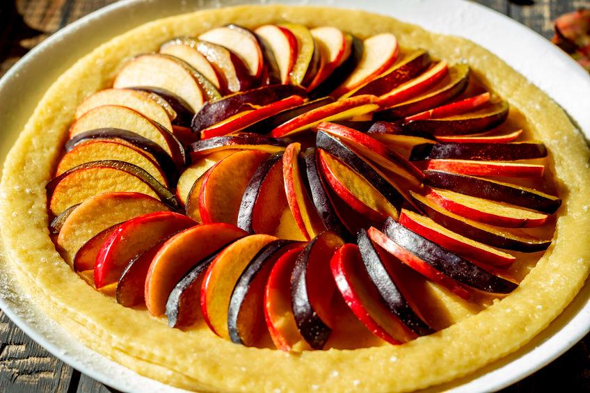 Cooking plum apple pie. Raw pie. Dough. Recipes. Vegetarian food. Dark photo.