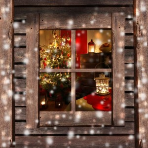 Christmas tree and fireplace seen through a wooden cabin window